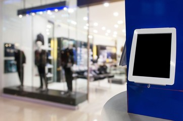 blank digital monitor or tablet on counter in front of men fashion clothes shop showcase in department store shopping mall, copy space for text or media content, marketing, advertisement concept