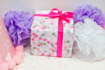 Closeup image of present and tissue pompoms for kid's birthday party