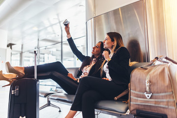 Two women talking selfie while waiting for a delay flight sitting with suitcases in airport terminal
