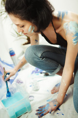 Woman sits in pofile and works on watercolor painting