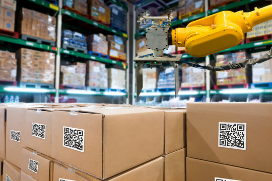 Smart logistic industry 4.0 , QR Codes Asset warehouse and inventory management supply chain technology concept. Group of boxes and Automation robot arm machine in storehouse.