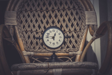 Vintage background with retro alarm clock on chair pattern background