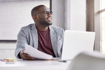Happy dark skined male manager wears classic suit, works on computer and with documents, sits at spacious cabinet, makes banking online. Cheerful middle aged African male owner of business company