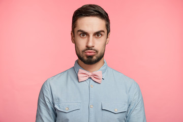 Serious brunet man dressed in formal shirt and bow tie, pouts lips, meets guests who came to congratulate him with anniversary, poses against pink studio background. People and emotions concept