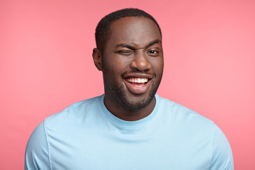 Cheerful plump middle aged dark skinned man blinks eye and has appealing smile, flirts with beautiful woman who stands before, tells jokes or funny stories, isolated over pink studio background.