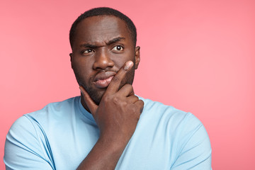 Portrait of serious dark skinned thoughtful male wears casual clothes, has pensive expression, isolated over pink background. Africam American plump man thinks about very importnat event in life