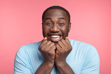 Cheerful emotional happy dark skinned male grins at camera, demonstrates white perfect teeth, keeps fists under chin, glad to recieve positive news that he will become father, isolated over pink wall