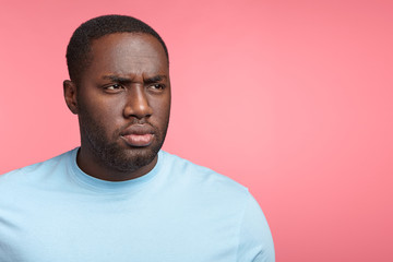 Horizontal portrait of black serious male has full lips, looks aside with thoughtful gloomy expression, feels frustrated and troublesome, poses against pink background with copy space for advertisment