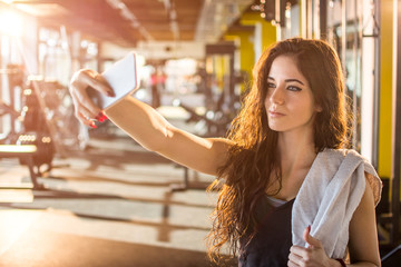 Young woman with towel around shoulder taking selfie photo after fitness workout in gym.