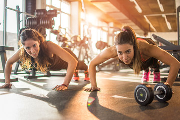 Two fit sporty girls doing push ups in the gym.