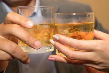 Close up of couple toasting whiskey glasses. (カップル乾杯シーン ウイスキー イメージ)