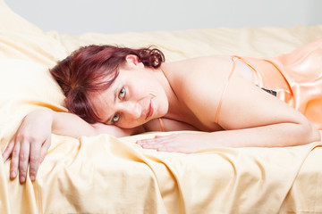 Sexy girl in peach-coloured combinations is lying on a bed