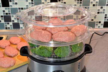 Preparation of meat steamed cutlets and broccoli vegetables in a steamer. Series.