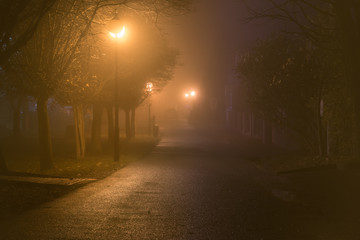 Dark alley in heavy fog iluminated by street lamps