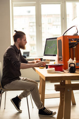 Full length portrait of concentrated young designer sitting in front of modern computer and prototyping 3D model, interior of spacious studio on background
