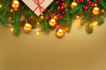Christmas background decoration with lights, gold balls, gift box and fir tree branches isolated on gold. Top view with blank space.