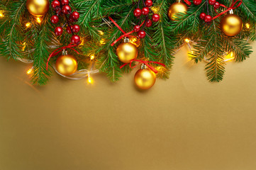 Christmas background decoration with lights, gold balls, berries and fir tree branches isolated on gold. Top view with blank space.