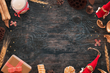 Christmas background with gold and red color decorations. Free space in the middle. Top view of black wooden desk.