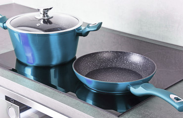 Frying pan and steel pot on modern induction cooktop