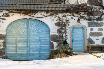 traditional farmhouse with blue door in winter