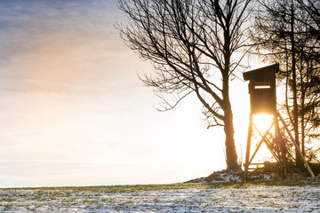 raised hunting stand in winter next to field