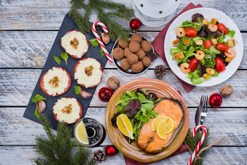 Christmas or New Year Family Dinner Setting Table Concept with Holiday Decoration. Delicious Roast Steak Salmon, Salade, Appetizers and Dessert on white wooden Background. Top view