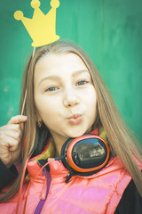 Portrait of a teenage girl with headphones and a paper crown and making a face, against a green  background