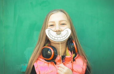 Portrait of a teenage girl with headphones and a paper smile and making a face, against a green  background