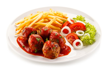 Roasted meatballs, chips and vegetables on white background