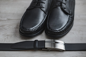 Men fashion. Men accessories. Black shoes and black belt . Still life. Business look on a wooden background