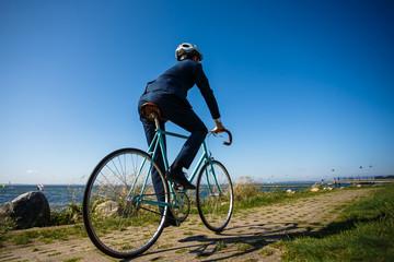 Businessman cycling at seaside