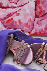 Women's accessories. Beautiful female shoes and purple scarf on a wooden background. Fashion look