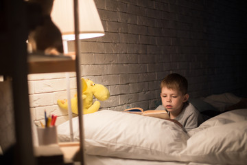 Portrait of cute little boy reading fairytales in bed under lamp light, propping book on pillow in dark room at night, copy space