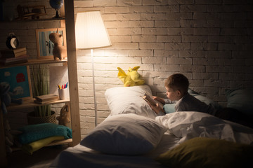 Side view portrait of cute little boy reading fairytales in bed under lamp light, propping book on pillow in dark room at night, copy space