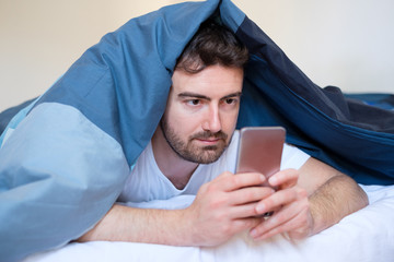 Man holding cellphone in hand lying in bed