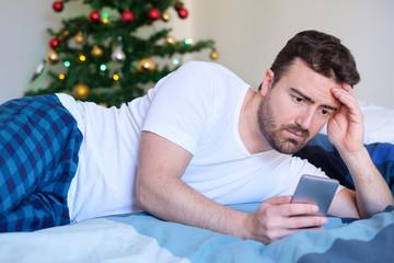 Worried man reading bad news on smartphone display