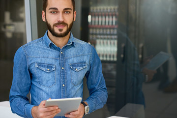 Portrait of bearded young man posing looking at camera standing against server cabinet, copy space