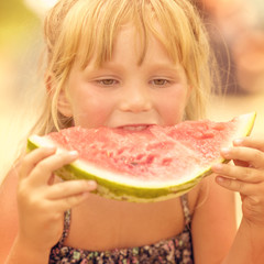 Little cute blond girl eating a slice of red watermelon on blurred background