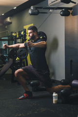 Muscular man workout on exercise machine