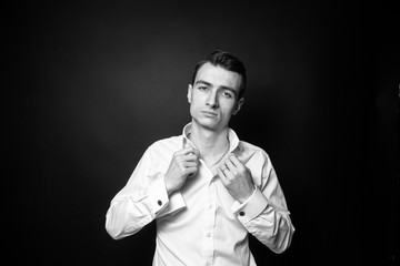 Black and white portrait of a young handsome man button up a shirt, standing and seriously looking at the camera, buttons undone, against plain studio background