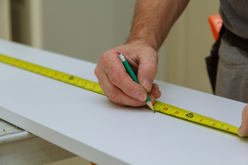 Close-up The man measures a wooden board with a ruler and marks with pencil
