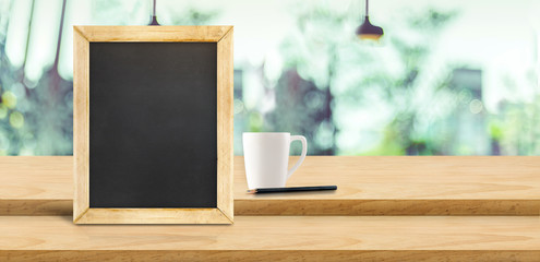 Blank blackboard and coffee cup on step podium wood table with blur garden cafe restaurant background bokeh,Mock up for display or montage of product,Banner or header for advertise on online media