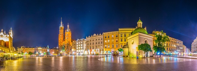 Fotorollo Krakau Night view of the rynek glowny main square with the church of Saint Mary and church of Saint Adalbert in the polish city Cracow/Krakow.