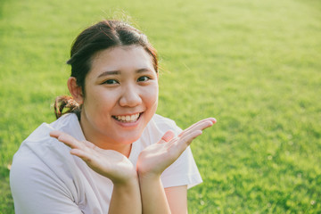 cute young innocent asian teen smile present her face on green grass background
