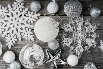 Silver and white Christmas balls, snowflakes and stars on a wooden background. Placer of various Christmas toys on old wooden boards. Christmas card. Christmas festive background. Top view.