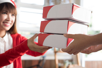 startup small business owner give parcel box to delivery man for sending to customer. woman's hand receive product from seller at shop.  Online selling, e-commerce, shipping concept