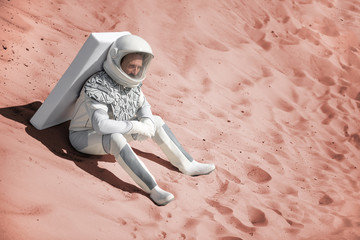 Mindful astronaut wearing white armor is sitting on sand and looking ahead with bewilderment. Copy space on right side