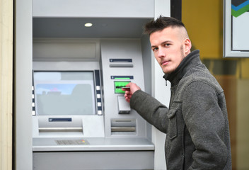 young man insert credit cart to atm