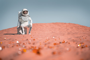 Cheerful spaceman wearing white armor is sitting on suitcase and looking at bright orange stones with smile. Portrait. Copy space on right side