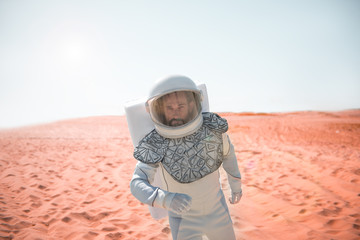 Serious cosmonaut wearing helmet is hardly moving though red sand and wind. He looking at camera with determination. Waist up portrait. Copy space on left side